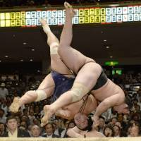 Look out below: Kotooshu (right) throws Myogiryu for a win by the narrowest of margins at the Autumn Grand Sumo Tournament on Wednesday.  | KYODO