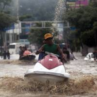 Dramatic rescue: A man on a jet ski evacuates residents in Acapulco, Mexico, after heavy rain struck the area Monday.   | AFP-JIJI