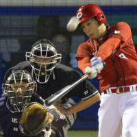 Helping his own cause: Carp starting pitcher Yusuke Nomura belts a three-run home run in the third inning against the Swallows on Thursday at Jingu Stadium. Hiroshima defeated Tokyo Yakult 12-6. | KYODO