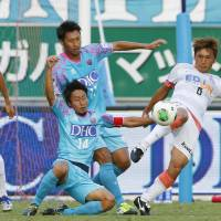 Evasive action: Sanfrecce Hiroshima's Toshihiro Aoyama (far right) moves to clear the ball during Sanfrecce's 2-0 win over Sagan Tosu on Saturday. | KYODO