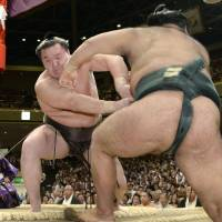 First impression: Yokozuna Hakuho (rear) shoves Takayasu out of the ring at the Autumn Grand Sumo Tournament on Sunday. | KYODO