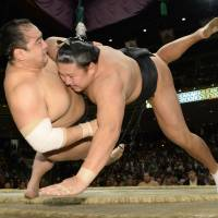 Flying tackle: Kyokutenho (right) takes down Aminishiki at the Autumn Grand Sumo Tournament on Monday. | KYODO