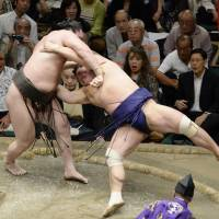 Hit the deck: Hakuho sends Myogiryu to the ground during their bout at the Autumn Grand Sumo Tournament on Sunday. | KYODO
