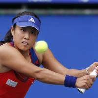 Through the pain barrier: Ayumi Morita plays a shot during her 7-6 (7-4), 6-3 win over Britain's Laura Robson at the Pan Pacific Open in Tokyo on Monday. | AP