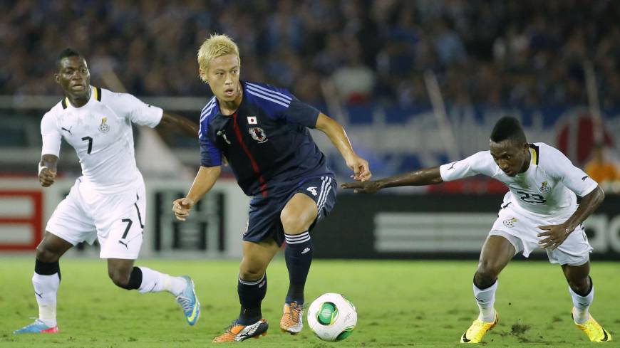 Quick adjustments: Japan's Keisuke Honda tries to move the ball past Ghana's Christian Atsu (7) and Harrison Afful during the first half of Tuesday's match. Honda scored Japan's third goal in the 72nd minute.