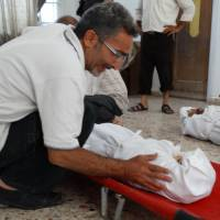 Misconduct of war: A Syrian weeps over the body of one of his children killed during an alleged toxic gas attack by pro-government forces in the Damascus suburb of eastern Ghouta in this photo released by the opposition Shaam News Network on Aug. 23. | AFP-JIJI
