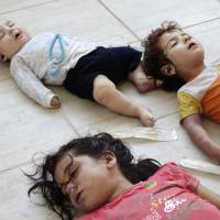 Tiny casualties: The bodies of a baby and two children, victims of a purported chemical weapons attack on Ghouta, Syria, are seen on Aug. 21. | AP