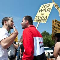 War of words: Protesters argue during demonstrations for and against a U.S.-led strike on Syria in front of the White House in Washington on Saturday. | AFP-JIJI