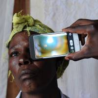 Eye opening: Using a special lens, a technician scans the eye of a woman with the 'Eye-Phone' smartphone application as she takes part in an ophthalmological study in the village of Kianjokoma, Kenya, last week. | AFP-JIJI