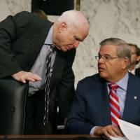 The Syria question: Arizona Sen. John McCain talks to Senate Foreign Relations Committee Chairman Robert Menendez in Washington on Wednesday. | GETTY/KYODO