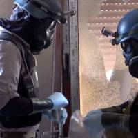 Probing for proof: Members of a U.N. team take samples from the ground in the Damascus area of Zamalka on Aug. 29 in this image taken from video obtained from the Shaam News Network. | AP
