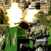 Gunning for the rebels: A Syrian solider fires a heavy machine gun during clashes with rebels in Maaloula village, northeast of the capital, Damascus, on Saturday. | AP