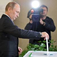 One president, one vote: Russian President Vladimir Putin casts his ballot at a polling station in Moscow on Sunday. | AP