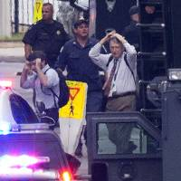 Narrow escape: People are escorted out of the building where a gunman went on a shooting rampage at the Washington Navy Yard in the U.S. capital on Monday. | AP