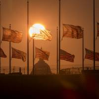 Moment of mourning: American flags surrounding the Washington Monument fly at half-staff Tuesday in the wake of the deadly shooting at the Washington Navy Yard. | AP