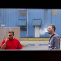 Vapor gets in your eyes: Two men smoke e-cigarettes on a work break. | BLOOMBERG