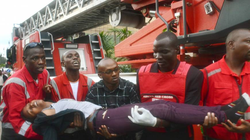 A woman who had been held hostage is carried by rescue personnel on Saturday after she was freed following a security operation.