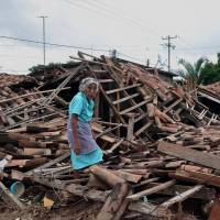 Scrap and flinders: A woman walks amid the wreckage of her home in the Agua Caliente district of Acapulco on Friday. | AFP-JIJI