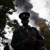 New tactic: A Kenyan security officer moves the crowd as thick smoke rises from the Westgate Mall in Nairobi on Monday. | AP
