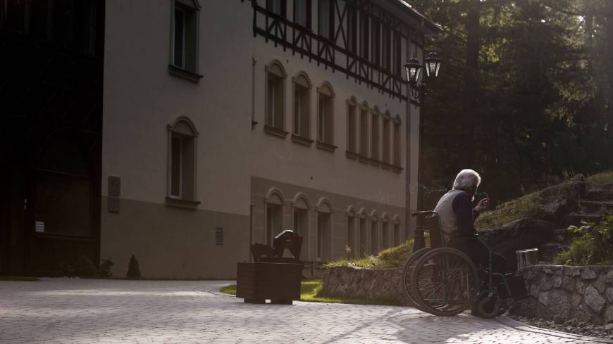Finding another way: A resident sits in a wheelchair and smokes a cigarette on the grounds of the care home where he lives in Szklarska Poreba, Poland, on Aug. 24. Polish nursing homes have seen a rise in Germans seeking affordable elderly care, while one German newspaper denounced it as 'gerontologic colonialism.'