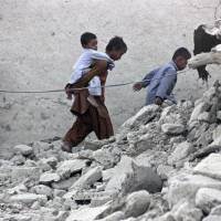 Crashing down: Survivors of a massive earthquake in Pakistan walk through the rubble of a mud house after it collapsed following a temblor in the town of Awaran in the southwestern province of Baluchistan on Wednesday. | REUTERS/KYODO
