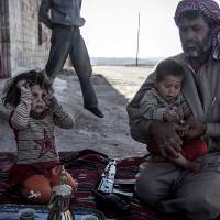 Friend or foe?: A Free Syrian Army fighter holds his son outside their home in Habit, Hama province, on Wednesday.   AP