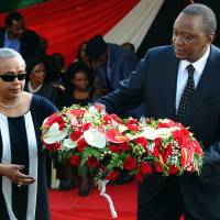 Touched by tragedy: Kenyan President Uhuru Kenyatta and his wife, Margaret, lay flowers during the funeral service of their nephew Mbugua Mwangi and his fiancee, Rosemary Wahito, in Nairobi on Friday after the two were killed in the Westgate Mall attack. | AFP-JIJI