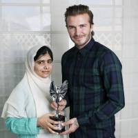 Standing out: Retired English soccer star David Beckham presents a Mirror Pride of Britain Teenager of Courage Award to Malala Yousafzai, the Pakistani schoolgirl who was shot by the Taliban for advocating education for girls. | AP
