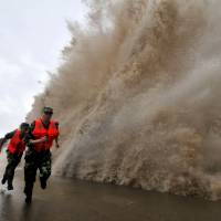 A step ahead: Men sprint along a pier as it is struck by a huge wave from Typhoon Fitow on Sunday, hours before it made landfall in Wenling, in China's Zhejiang province, early on Monday. | AFP-JIJI