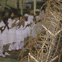 Detained: In this photo reviewed and approved by the U.S. military, detainees pray before dawn near a razor-wire fence at the U.S. Navy's Guantanamo Bay prison in May 2009. | AP