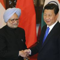Good neighbors: Chinese President Xi Jinping greets Indian Prime Minister Manmohan Singh in Beijing on Oct. 23. China and India signed an accord last week on border defense. | AP