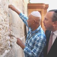 Holy: Hip-hop and fashion mogul Russell Simmons slips a note inscribed with a prayer into the Western Wall, Judaism's holiest site, in Jerusalem in 2012. | BLOOMBERG