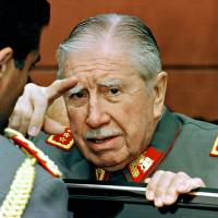Usurper: Gen. Augusto Pinochet talks to an attendee at a military school parade in Santiago, Chile, on Aug. 23, 1997. | BLOOMBERG