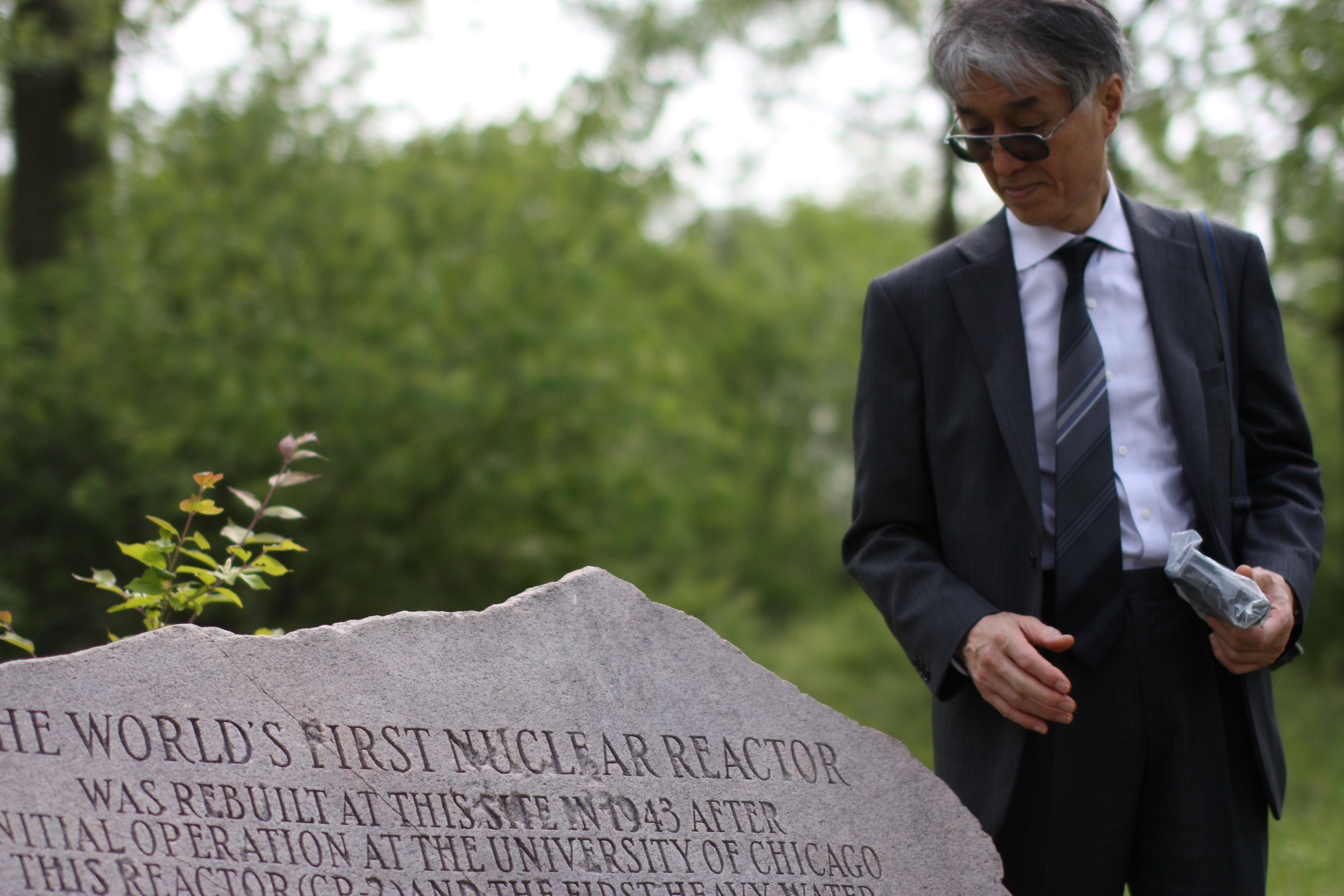 Entombed: Kyoto University nuclear physicist Hiroaki Koide takes radiation readings with a Geiger counter at a stone marker indicating the burial site of the world