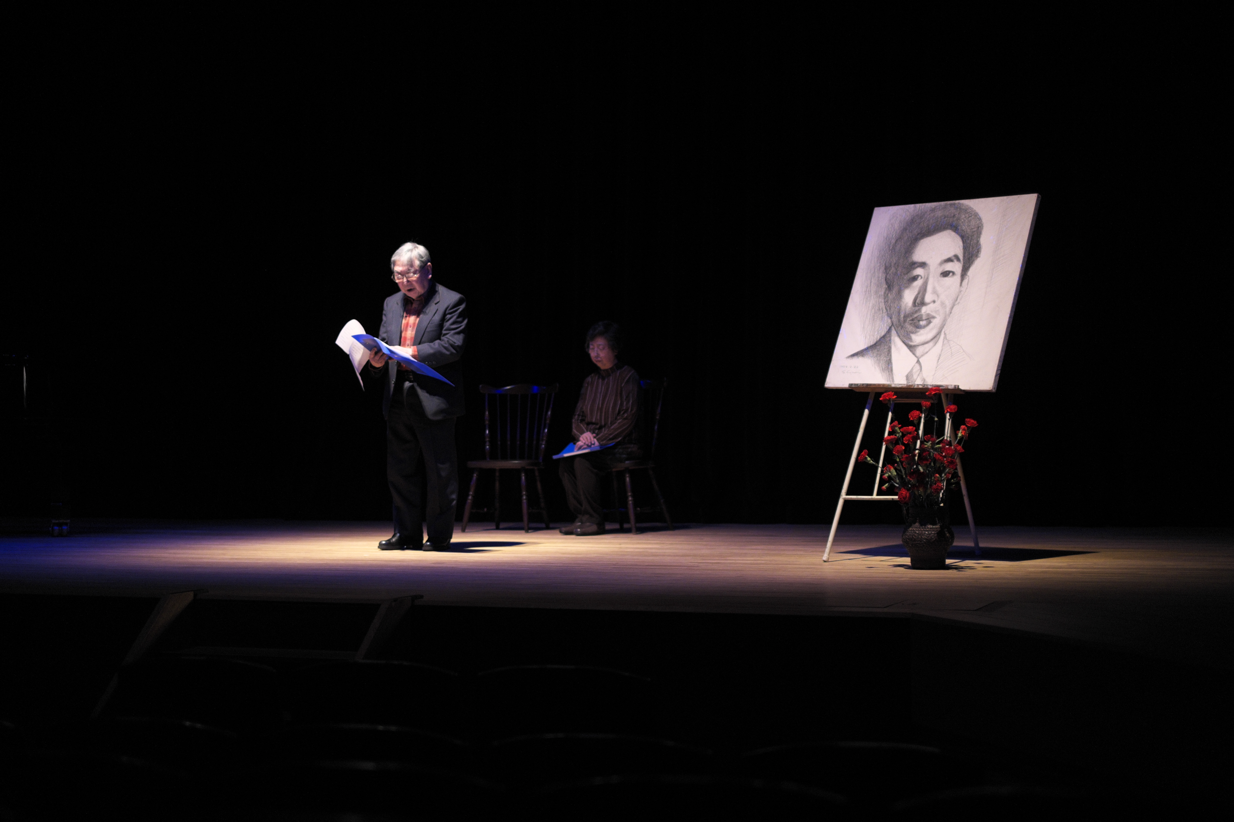 Ceremony: Standing by a portrait of the late proletarian writer Takiji Kobayashi, Takiji-sai chairman Katsuo Terai reads during an evening commemorating the 80th anniversary of the author