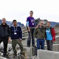 Family affair: Left to right, OGA for Aid's Jesse Ortiz, Peter Watabe, Angela Ortiz, Erwin Ortiz. and Aika Ortiz stand amid the ruins of Minamisanriku, Miyagi Prefecture, in March 2011. | COURTESY OF OGA FOR AID