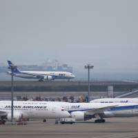 Coveted slots: A Boeing 787 Dreamliner operated by All Nippon Airways Co. lands at Haneda airport in Tokyo in late May. Japan Airlines Co. and ANA Holdings Inc. are fighting over additional slots at the airport, a dispute that is starting to include global airline partnerships. | BLOOMBERG