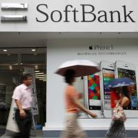 Wrong number: Pedestrians walk past a SoftBank Corp. store in Tokyo. The mobile phone company has been hit by a new scandal centered on its erroneous credit-rating of its customers. | BLOOMBERG