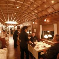 First-class fare: Foreign media members try out the services in the dining car of the Seven Stars luxury train during a recent demonstration run by Kyushu Railway Co. | JR KYUSHU/KYODO