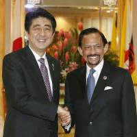Power shake: Prime Minister Shinzo Abe and Sultan Hassanal Bolkiah of Brunei shake hands ahead of their meeting in Brunei on Wednesday. | KYODO