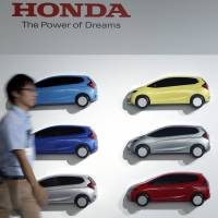 Take your pick: An employee walks past a display showing the colors available for Honda Motor Co.'s new hybrid Fit at the vehicle's launch in Urayasu, Chiba Prefecture, on Sept. 5. | BLOOMBERG