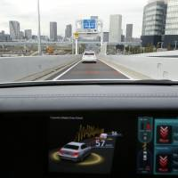 The future is here: A monitor displays the Cooperative-adaptive Cruise Control technology installed in a Lexus vehicle equipped with the Automated Highway Driving Assist support system as it is escorted by a Prius (top) at an expressway exit during a media briefing Thursday in Tokyo on Toyota's advanced technologies. | BLOOMBERG