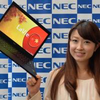 Light as a leaf: A model holds up NEC Personal Computer Ltd.'s 795-gram Lavie Z LZ750/NS, the world's lightest 13.3-inch notebook computer, in Tokyo on Tuesday. | AFP-JIJI