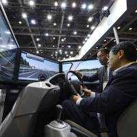In for a spin: A visitor tries out a Honda Motor Co. driving simulator at the ITS World Congress Tokyo 2013 at Tokyo Big Sight in Koto Ward on Tuesday. | BLOOMBERG