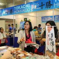 Foodies: Visitors ask questions at the Hokkaido booth of the 'Oishii Japan' food exhibition that opened Thursday in Singapore. | KYODO