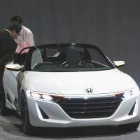 Drop top: Members of the media look at a Honda S660 concept sports car in Tokyo on Oct. 16. The mini convertible will premier at the Tokyo Motor Show on Nov. 20. | BLOOMBERG