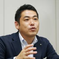 Luxury on rails: Yoshio Naka, deputy head of Kyushu Railway Co.'s Seven Stars cruise and sleeper train project, is interviewed in Fukuoka. Right:  JR Kyushu's new luxury train arrives to a large crowd at Nagasaki Station on Saturday. | KYODO