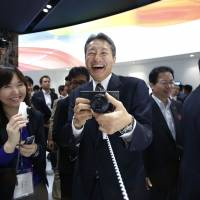 Hybrid: Kazuo Hirai, chief executive officer of Sony Corp., tries out a Sony Xperia Z1 smartphone with the Sony DSC-QX100 smartphone attachable lens-style camera at the CEATEC Japan 2013 trade show in the city of Chiba on Oct. 1. | BLOOMBERG