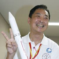 Aiming high: Yasuhiro Morita, head of the development team of the Epsilon rocket, is seen with a miniature replica of the new solid-fuel vehicle. | KYODO