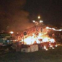 Deadly inferno: A photo taken by a witness shows a food stall engulfed in flames after a can of gasoline to refuel an electricity generator at the stall exploded at a fireworks event Aug. 15 in Fukuchiyama, Kyoto Prefecture. | KYODO